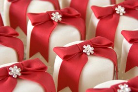 Mini cakes in white fondant with red bows and  brooches.