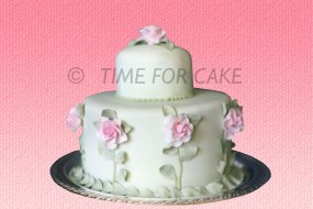 2 tier round wedding cake with handmade sugar roses around side of bottom tier plus a rose on top