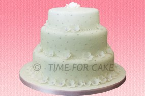 3 tier round cakes with dots of icing and finished with sugar blossoms on all tiers