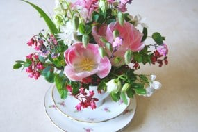 Table arrangement in a vintage china cup by The Flower Hive