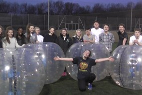 Group of Girls and Boys With Zorbs at a 18th Birthday Party with the Party Girl crouching in front of the group with her arms outstretch.
