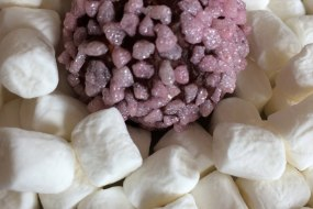 Champagne truffle coated in strawberry sugar on a bed of mini marshmallows