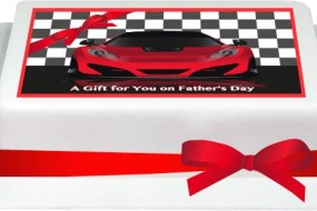 Printed topper of a red racing car on a rectangular cake finished with red ribbon