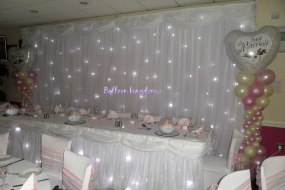 Starlight back drop and table skirt with chair covers and balloon columns