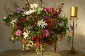 Autumn table arrangement with berries, herbs and wildflowers