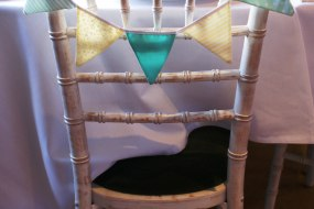 Handmade miniture bunting hanging on the back of a chivari chair