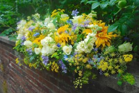 A long arrangement for a summer wedding in shades of yellow, blue and white