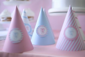 Pastel pink and blue party hats saying Happy day
