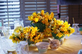3 green vintage vases filled with daffodils and yellow tulips of a dinner table