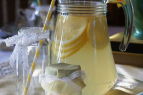 Glass jug filled with traditional lemonade. Wedding favour jam jars filled with sweets.