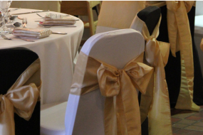 Black and White Chair Covers with Gold Sashes