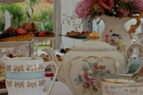 An afternoon tea with beautiful vintage china, table decorations and chair sashes.
