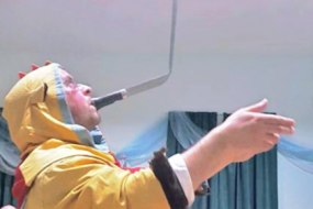 The Conwy Jester balancing a sword on the tip of a knife held in teeth.