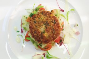 Indian spiced potato and tofu cake with a cherry tomato, cucumber and toasted cumin seed salad with a curried yoghurt