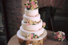 A Beautiful Four Tier weddig cake in a simple blush pink theme, decorated with fresh flowers, by The Daisy Chain Bakery