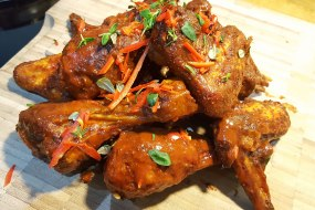 Slow smoked chicken wings tossed in hot sauce. Fresh thyme and chilli garnish