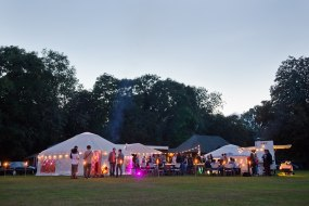 A party with yurts, wood fired pizza vans, decorative outdoor lamps, and groups of people.