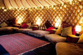 A cosy yurt with cushions, warm lighting and rugs.