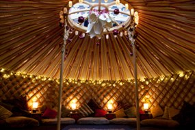 A cosy yurt with cushions, warm lighting and rugs