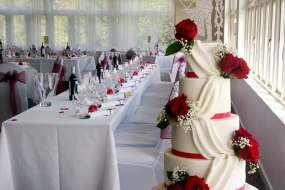 White wedding cake with red roses in Collingtree Golf Club