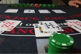 Table top view of chips, cards and one of our Croupiers dealing blackjack