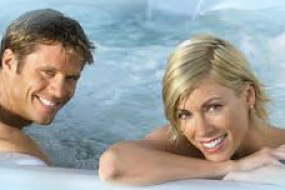 Couple relaxing in a hot tub from K & S Hot Tubs