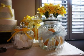 3 large glass jars filled with lemons and mini miragues, tied with yellow ribbon. Vases filled with daffodils.