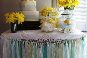 small table with 3 tier cake and vintage jars and vases filled with daffodils