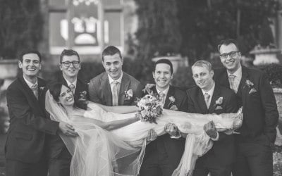 black and white bride laying across groomsmen