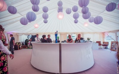 Paper lanterns, linings, round bar in a wedding marquee