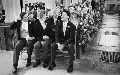 Groom and groomsmen laughing in church prior to wedding ceremony
