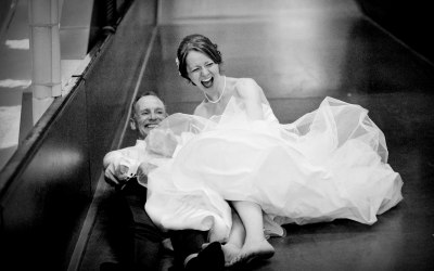 Bride and father enjoying big slide