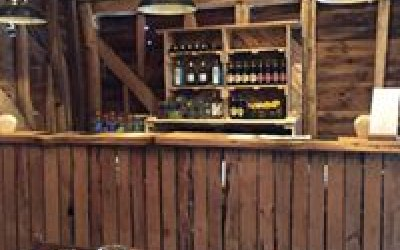 Rustic wooden bar at a wedding in a barn.