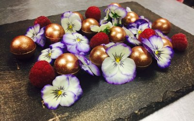 Mixed chocolate truffles with raspberries and edible flowers