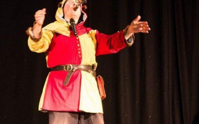 The Conwy Jester balances a lit candle stick on a knife held in mouth