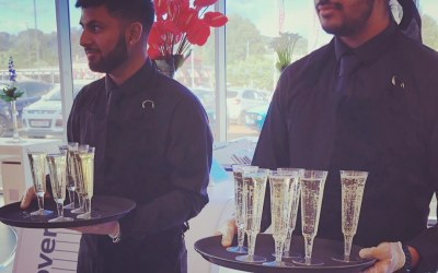 Team members serving Prosecco