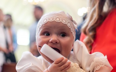 Baby Hilda munching on her Baptism candle at her special event!