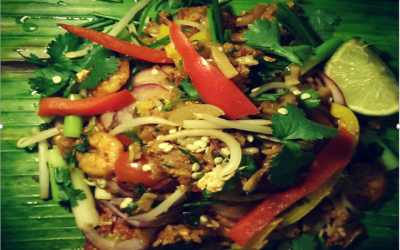 Spicy Prawns - Flat Rice noodles lightly chilli spiced with Spicy Prawns, beansprouts, Peppers and spring onions which is freshly wrapped and roasted in Banana Leaf (Vegetarian option available)