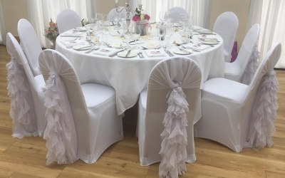 White chair covers with white chiffon hoods and ruffles