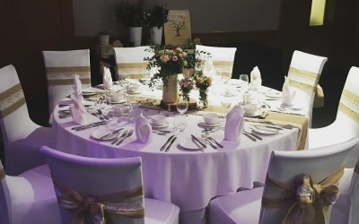 White chair covers and hessian with lace sashes and table runners