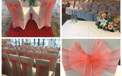 White chair covers and coral organza sashes