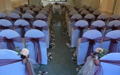 White chair covers and burgundy organza sashes