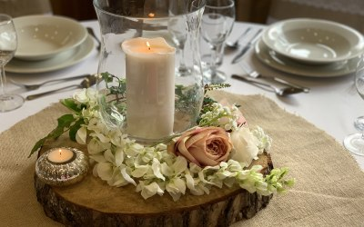 Hurricane vase and candle on wooden log