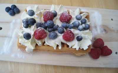 waffle with whipped cream, raspberries, blueberries and caster sugar topping