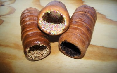 chimney cakes with oreo, nibbed nuts and rainbow toppings