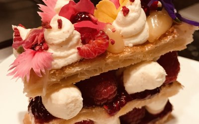 A decadent dessert of handmade lemon & Raspberry Millefeuille with edible flowers