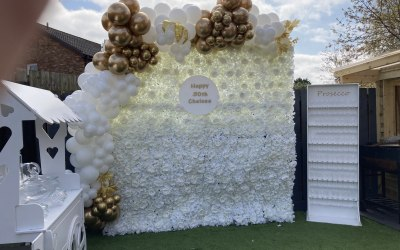 White flower wall with personalised sign and balloon garlands