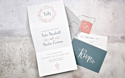 Folded illustrated invitation tied with string and monogram tag