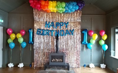 Rainbow themed 1st birthday balloon display