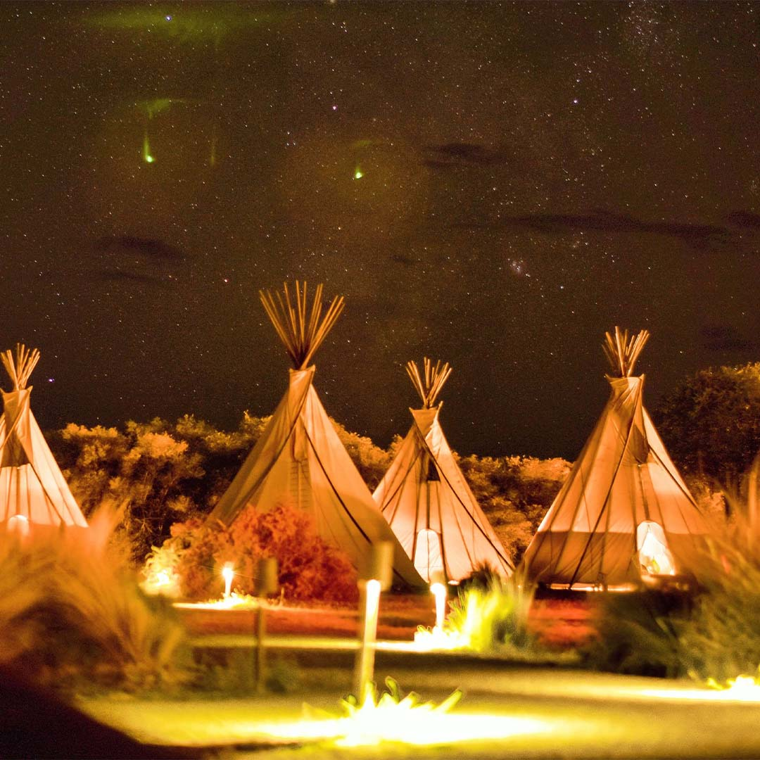 Several glamping tipi tents at night with the stars shining